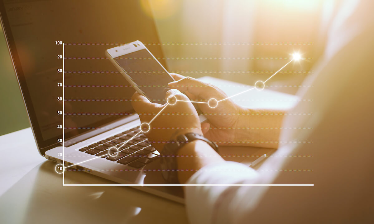 graphicstock-businessman-using-smart-phone-and-laptop-with-graph-statistical-analysis-business-success-concept_r_zdRiDlsl
